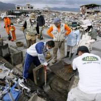 Volunteers work in the tsunami-hit town of Otsuchi, Iwate Prefecture, in May 2011,  just months after a devastating tsunami and earthquake hit and devastated the eastern seaboard of the Tohoku region. Sources Thursday said the Red Cross plans on adopting the first-ever charter to guarantee the rights of volunteers later this year. | KYODO