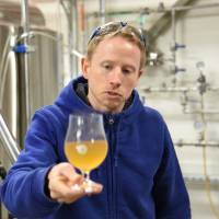 Chris Hainge, Kyoto Brewing co-founder and head brewer, shows off a sample early in the brewing process. | SATOKO KAWASAKI