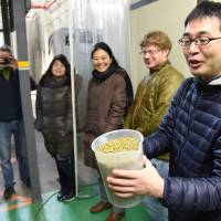 Hiroyuki Tomie, of the Japan Times beer club,  holds a container of the hops, prior to them being added them to the brew kettle.   SATOKO KAWASAKI