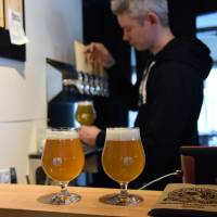 Ben Falck — one of the founders of Kyoto Brewing Co. — pours beers in the brewery's tasting room.  | SATOKO KAWASAKI