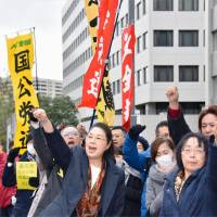 Betrayal: All-Japan 'Consider Karoshi' Family Association members protest outside the prime minister's official residence in Tokyo against what they call the 'legalization of the karōshi  line' agreed between the government, Keidanren and Rengo. | KYODO