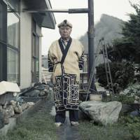 Nibutani, Hokkaido, 2015. Kazunobu Kawanano is a proud Ainu Ekashi (elder) and an active member of the local Ainu community. He is pictured in front of his home, wearing a traditional Attus robe that his wife, Motoko, weaved for him. | LAURA LIVERANI / LUNCH BEE HOUSE