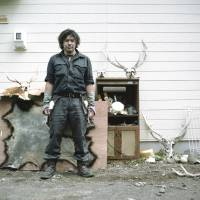 Biratori, Hokkaido, 2015 Monbetsu, a professional bear and deer hunter stands at his home with his hunting trophies. | LAURA LIVERANI / LUNCH BEE HOUSE