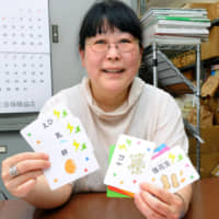 Be prepared: Tomomi Akagi of the Tokyo-based NPO Atopicco holds up cards used to teach children with allergies to understand labels identifying common culinary culprits. Food allergy sufferers living in Japan recommend visitors carry around a card with their allergy information written on it in Japanese. | KYODO