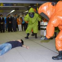 Fire Department officers take part in an anti-terrorism drill in Tokyo in July 2004. | AP
