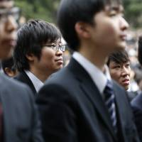 College students listen to a guest speaker during a ceremony to launch their job search at Tokyo's Hibiya Park on Wednesday. | AP