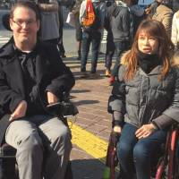 Unimpeded access: Paralympic athlete Kazumi Nakayama attends a tour of Tokyo's Shibuya Ward led by Accessible Japan's Josh Grisdale (left). | MICHAEL GILLAN PECKITT