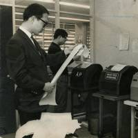 Reporters check the news on wire service machines in 1967.