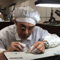 Katsuo Saito, another master craftsman of Seiko, assembles a watch at Shizukuishi Watch Studio in March. | CHIHO IUCHI