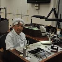 At the Shizukuishi Watch Studio, Katsuo Saito sits with a smile of pride at a customized urushi-lacquered workbench made by local manufacturer Iwayado Tansu. | CHIHO IUCHI