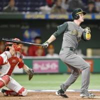 Australia's James Beresford bashes an eighth-inning grand slam against China in a World Baseball Classic game at Tokyo Dome on Thursday night. Australia defeated China 11-0. | KYODO