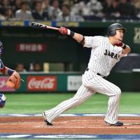 Japan's Yoshitomo Tsutsugo hits a first-inning single against Cuba in the teams' WBC opener at Tokyo Dome on Tuesday.   AFP-JIJI