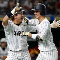 Japan's Seiji Kobayashi (right) celebrates with teammate Nobuhiro Matsuda after hitting a two-run homer in the bottom of the second inning of a World Baseball Classic Pool B first-round game against China on Friday night at Tokyo Dome. Japan defeated China 7-1.  | AFP-JIJI