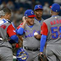 Cuba manager Carlos Marti (center) talks with starter Vladimir Banos during the fifth inning. | AP