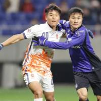 Gamba's Yasuyuki Konno (right) competes against Jeju's Lee Chan-dong during their Asian Champions League match on Wednesday in Suita, Osaka Prefecture. | KYODO