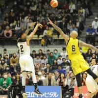 Tokyo's Diante Garrett attempts a last-second shot over Shibuya's Robert Sacre on Sunday at Aoyama Gakuin University Memorial Hall. Garrett made the shot, leading the Alvark to a 66-64 win over the Sunrockers. | B. LEAGUE