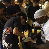 Larry Williams signs autographs for students earlier this month in Kansai. Between 700 and 800 Japanese youth attended his basketball clinics in Osaka and Kobe. | LARRY WILLIAMS