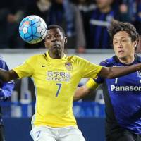 Jiangsu Suning's Ramires controls the ball as Gamba Osaka's Yasuyuki Konno (left) and Yasuhito Endo (right) defend during their Asian Champions League game on Wednesday. | AFP-JIJI