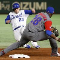 Israel's Sam Fuld slides safely back to first as Cuba's William Saavedra prepares to tag on Sunday at Tokyo Dome. | AP