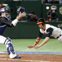 Catcher Seiji Kobayashi, seen here waiting for the ball against the Netherlands in a World Baseball Classic second-round game on March 12 at Tokyo Dome, has been a key member of the Samurai Japan team thus far in the tournament. | AP