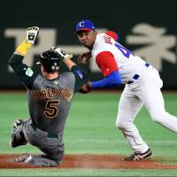 Cuba's Alexander Ayala turns a double play as Australia's James Beresford slides into second base in the sixth inning of their World Baseball Classic first-round game at Tokyo Dome on Friday. | AFP-JIJI