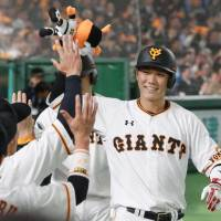 The Giants' Hayato Sakamoto is congratulated by teammates after hitting a two-run home run in the fifth inning. | KYODO