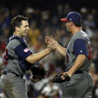 Buster Posey (left) and Luke Gregerson on the United States celebrate after beating Japan on Tuesday. | AP