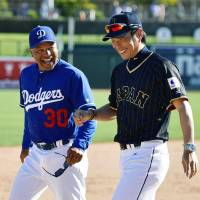 Japan manager Hiroki Kokubo (right) shares a joke with Los Angeles Dodgers counterpart Dave Roberts after their game on Sunday in Glendale, Arizona. | KYODO