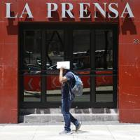 A man shields his face from the sun as he walks past the offices of tabloid newspaper La Prensa on Paseo de la Reforma in Mexico City Monday. The mystery of Tom Brady's missing Super Bowl jersey led police all the way to Mexico, and authorities were investigating a former tabloid newspaper executive's possible role in the case. | AP