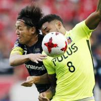 Gamba Osaka's Yasuhito Endo (left) and Urawa Reds' Rafael Silva compete for the ball during their 1-1 draw in the J. League on Sunday.   KYODO