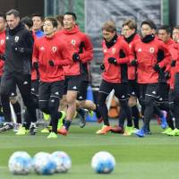 Japan's players jog around the Saitama Stadium pitch on Monday in preparation for Tuesday's night's World Cup qualifier against Thailand. | KYODO