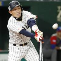 Pinch hitter Seiichi Uchikawa hits a sacrifice fly in the eighth inning of Japan's 8-5 win over Cuba on Tuesday night during the World Baseball Classic at Tokyo Dome. | KYODO