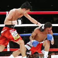 WBC bantamweight champion Shinsuke Yamanaka (left) hits Mexican challenger Carlos Carlson with his famous left hand in the seventh round of their fight on Thursday. | AP