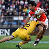 The Sunwolves' Ryohei Yamanaka is tackled by Dane Coles of the Hurricanes during their match on Saturday. | AFP-JIJI