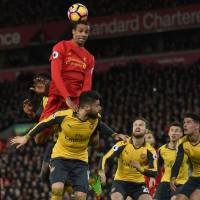 Liverpool's Joel Matip jumps for a header during the Reds' 3-1 win over Arsenal at Anfield on Saturday. | AFP-JIJI