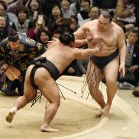 Shohozan shoves Kakuryu out of the raised ring on Friday at the Spring Grand Sumo Tournament in Osaka. | KYODO