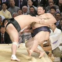 Harumafuji (left) forces rival yokozuna Kisenosato out of the raised ring on Friday at the Spring Grand Sumo Tournament in Osaka. | KYODO