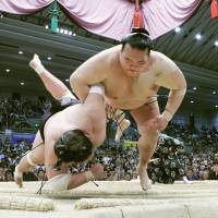 Kisenosato (right) throws Terunofuji to the ground during their title-deciding playoff bout at the Spring Grand Sumo Tournament in Osaka on Sunday. | KYODO