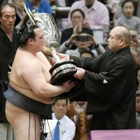 Kisenosato is presented with the winner's trophy after beating Terunofuji in a playoff at the Spring Grand Sumo Tournament on Sunday. | KYODO
