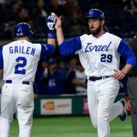 Israel's Ike Davis (right) is congratulated by teammate Blake Gailen after arriving at home plate following a double by catcher Ryan Lavarnway during their World Baseball Classic second-round game against Cuba at Tokyo Dome on Sunday. | AFP-JIJI