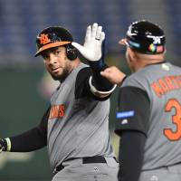 Wladimir Balentien of the Netherlands acknowledges first base coach Wim Martinus after hitting a single in the top of the third inning during their team's 12-2 win over Israel in the second round of the World Baseball Classic on Monday at Tokyo Dome. | AFP-JIJI