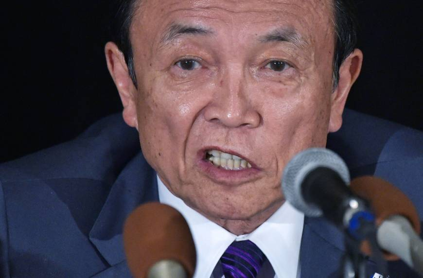 Finance Minister Taro Aso holds a news conference in Washington on Friday. | AFP-JIJI