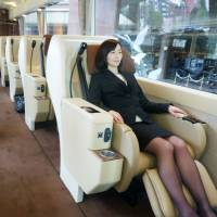 A woman tries out a seat in a new luxury tour bus Wednesday in Tokyo. Travel agency JTB Corp. said it will start selling related tours this month. | KYODO