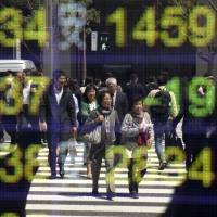 People's reflections are seen on an electronic stock indicator at a securities firm in Tokyo on Thursday.   AP