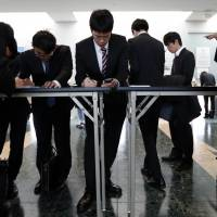 University students fill out registration forms at a job fair hosted by Mynavi Corp. in Tokyo in March. | BLOOMBERG