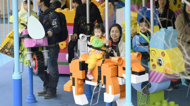 Children ride a carousel at Legoland Japan in Nagoya on Saturday.