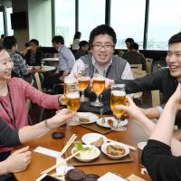 SoftBank employees toast at a company cafeteria in Tokyo on Feb. 24 as the nation's Premium Friday initiative kicked off. Firms are encouraged to allow staff to finish work early on the last Friday of the month in a bid to help spur consumption. | KYODO