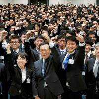 Panasonic Corp. President Kazuhiro Tsuga (front row, center) is surrounded by new employees during a welcoming ceremony on their first day of work in Hirakata, Osaka Prefecture, on Monday. | KYODO