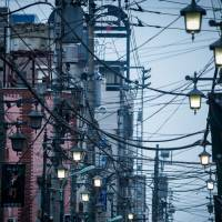 A web of cables is seen hanging from poles along a street in Hachioji, Tokyo. | BLOOMBERG
