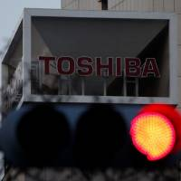 The Toshiba Corp. logo is seen behind a traffic light at the company's headquarters in Tokyo on Wednesday. | REUTERS